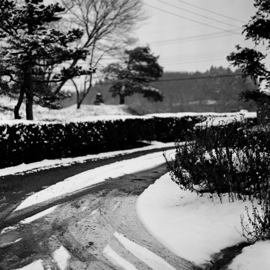 雪にタイヤの跡が残った砂利道