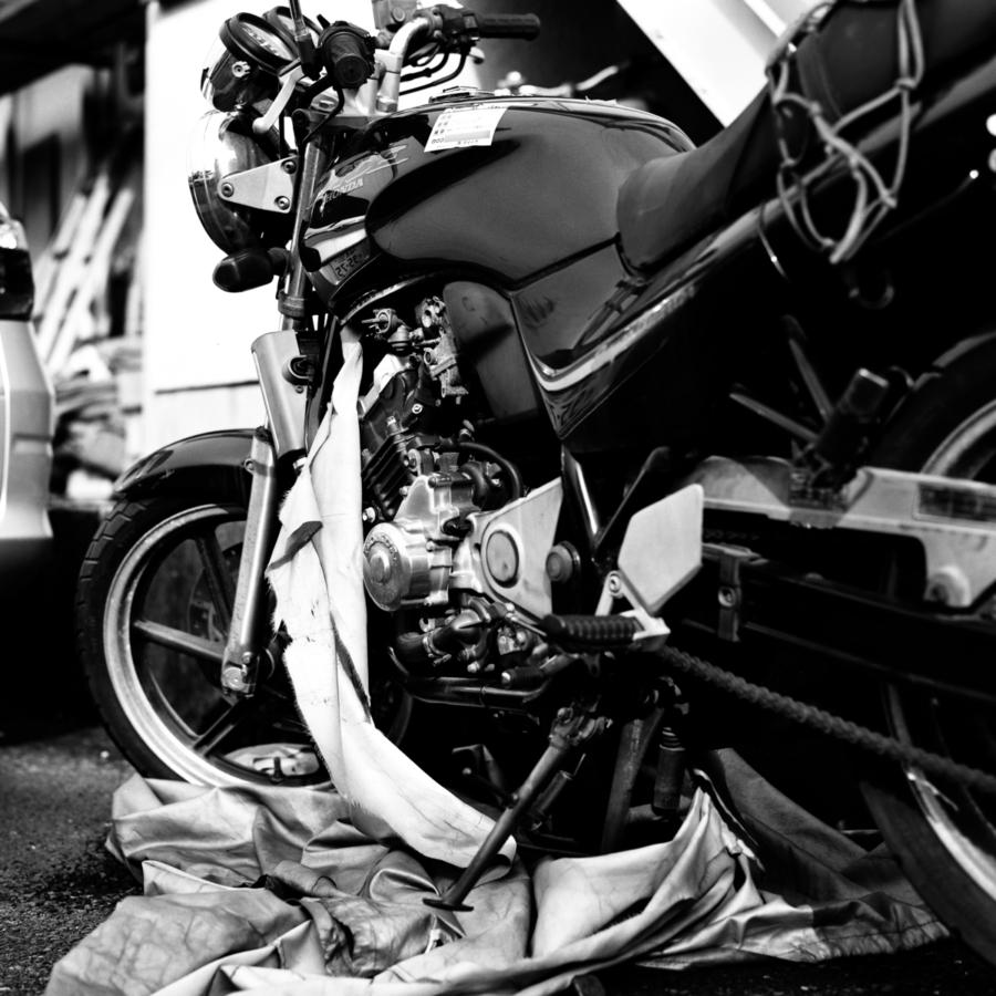 破れたバイクカバーとむき出しのエンジン